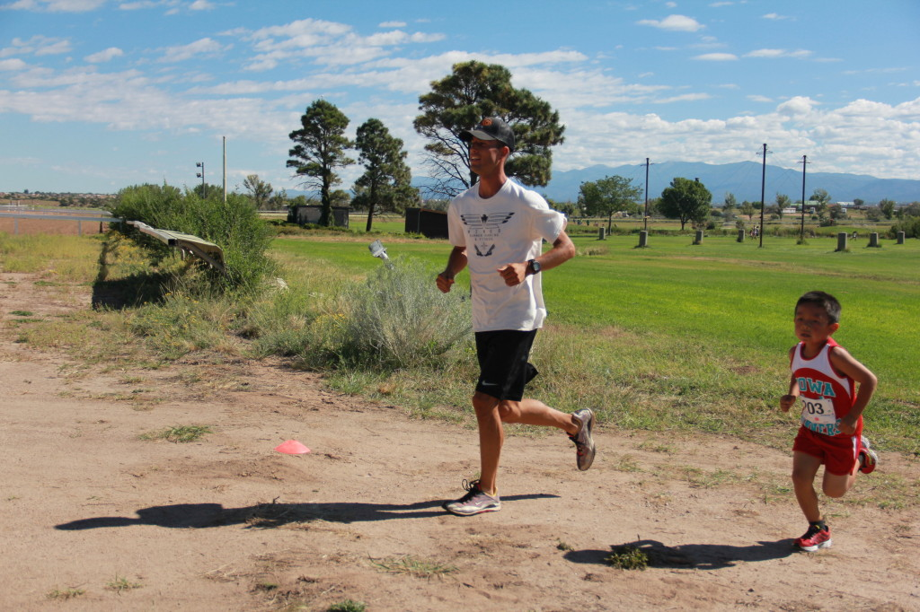 Wings summer facilitator and 2014 Indian Market 5K winner, Andy Yazzie, trots alongside Wings summer R&F Camp participant and Kids 2K winner, Brian Madalena (age 6), as he high gears past the first kilometer mark.